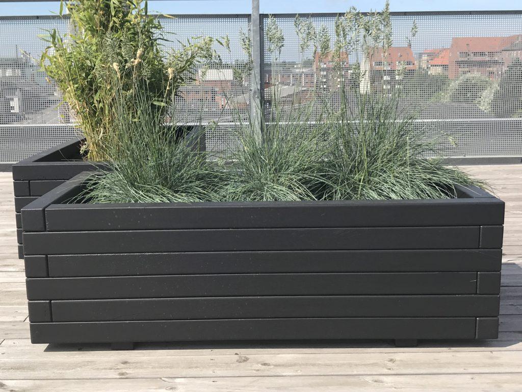 Hjalmar plantekasser set tæt på i behandlet sort træ