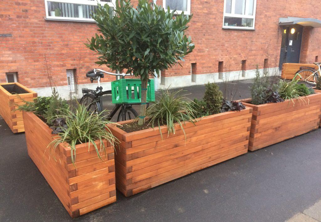 Teak plantekasser stående foran lejlighedskompleks set tæt på